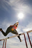 Athlete jumping hurdle — Stock Photo