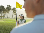 Golfer holding flag — Stock Photo