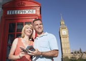 Couple with guidebook by London phone booth — Stock Photo
