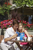 Couple sitting at outdoor cafe laughing — Stock Photo