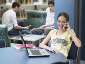 Girl using cell phone in library — Stock Photo