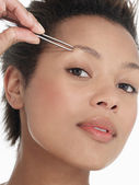 Young Woman plucking Eyebrows — Stock Photo