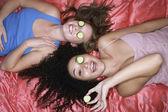 Tienermeisjes liggen met komkommers in ogen — Stockfoto