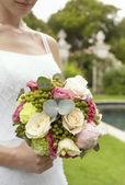 Bride in garden holding bouquet — Stock Photo