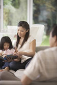 Mother Sitting on sofa Holding Page for Daughter — Stock Photo