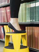 Woman standing on stool reaching for book — Photo