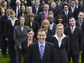 Business people standing on lawn — Stock Photo