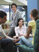 Teenagers talking in library — Stock Photo