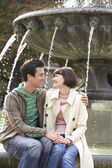 Embracing couple sitting on fountain — Stock Photo