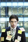 Businessman covered with Post-It notes — Stock Photo