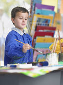Boy painting in art class — Stock Photo