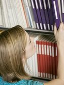 Girl reaching for book — Stock Photo