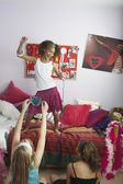 Girl standing on bed singing — Stock Photo