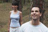 Couple in Forest Leaning on Trees — Stock Photo