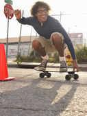 Man crouching on skateboard — Stok fotoğraf