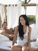 Couple on bed on beach — Stock Photo