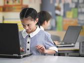 Schoolgirl using laptop — Stock Photo