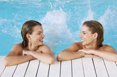 Women in pool splashing feet — Stock Photo