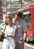 Vacationing couple reading map — Stock Photo