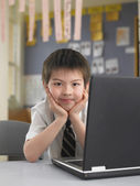 Schoolboy sitting by laptop — Stock Photo
