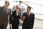 Businesspeople arriving from helicopter — Stock Photo