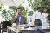 Businessman using mobile phone at outdoor cafe — Stock Photo