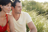 Couple Sitting in tall grass — Stock Photo
