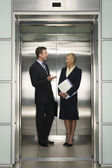Businesspeople Talking in Elevator — Stock Photo