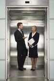 Hommes d'affaires parler dans l'ascenseur — Photo