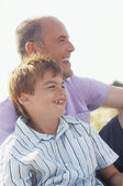 Father and Son sitting on beach — Stock Photo