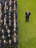 Business man standing next to large group — Stock Photo