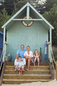 Family sitting in beach hut — Stock Photo