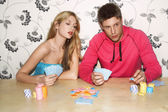 Couple on sofa playing cards — Stock Photo