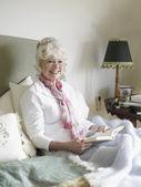 Mulher sênior na cama lendo o livro — Fotografia Stock