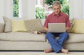 Man using laptop sat on sofa — Stock Photo