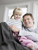 Girl sitting in father's lap — Stock Photo