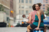 Couple riding on moped in street — Stock Photo