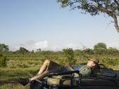 Adult man lying on bonnet — Stock Photo