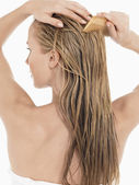Young Blond Woman Combing Hair — Stock Photo