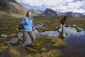 Two hikers wading through pond — Stock Photo