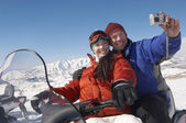 Paar zittend op de sneeuwscooter — Stockfoto