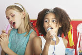 Girls using brushes microphones — Stock Photo