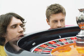 Hopeful men crouching at roulette wheel — Stock Photo