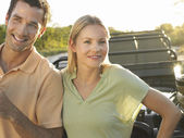 Couple standing by jeep — Stock Photo