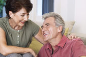 Couple sitting smiling looking into eyes — Stock Photo