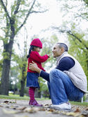 Girl playing with father in park — Stock Photo