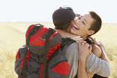 Couple of hikers hugging in field — Stock Photo