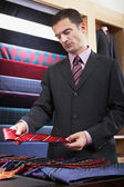 Businessman selecting tie in clothes store — Photo