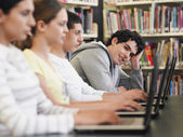 Students using laptops in library — Stock Photo
