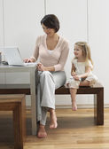 Mother showing daughter laptop — Stock Photo